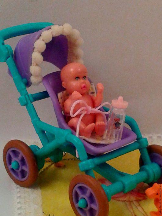 Малыш  в коляске с аксессуарами.