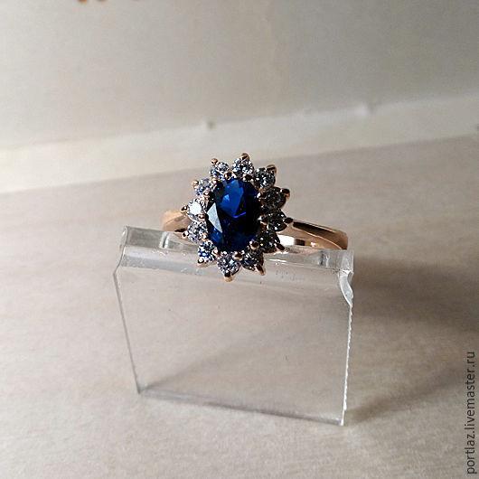 Кольцо с сапфиром и фианитами  в стиле помолвочного кольца принцессы Дианы и Кейт Миддлтон выполнено из ювелирного сплава с позолотой 585 пробы. 17 размер.