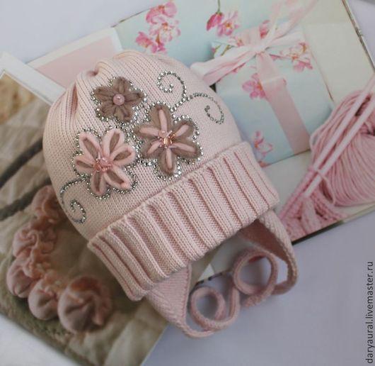 Изящная нежная шапочка связана из итальянской шерсти мериноса экстрафайн.На шапочке вышиты цветочки , которые дополнены стразами, бусинами, бисером. Цвет нежно-розовый.