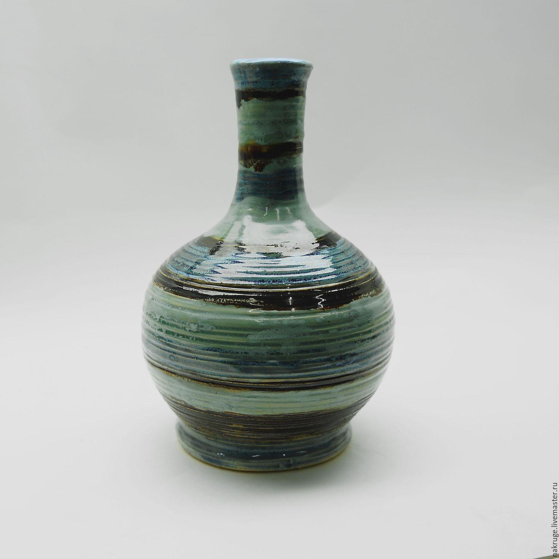 Красивая гончарная ваза цвета которой,  размытыми пятнами ложась на фактуру, привносят движение в облик интерьера. Бирюзовая, зеленая, синяя полосы струятся как как туман меж коричневых ветвей.