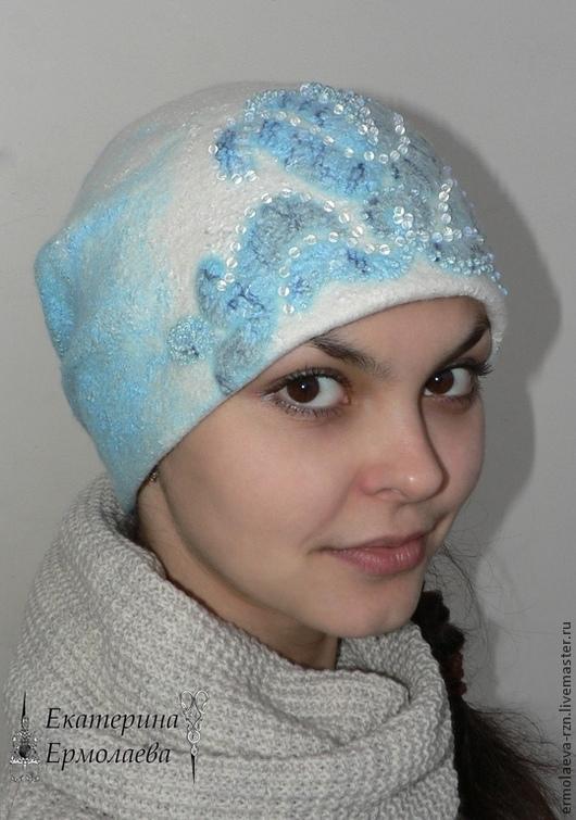 Теплая, мягкая зимняя женская валяная шапка `Зимняя сказка` сваляна из шерсти меринос 18 микрон трех цветов: белого, светло-голубого и темно-голубого и отделана волокнами вискозы и шелка тех же оттенк
