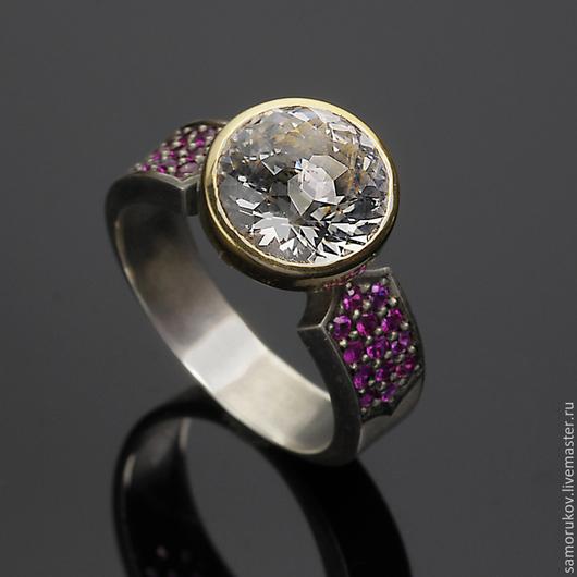 Кольцо изготовлено из серебра 925 и золота 750 проб. Бесцветный топаз массой 4.5 ct и натуральные рубины 0.4 ct. Размер кольца 17.4
