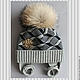 Тёплая, стильная зимняя двойная шапочка для мальчика. Шапочка связана в технике жаккард из двух цветов светло-серый и тёмно-синий.Шапочка дополнена стильной металлической нашивкой и енотовым помпоном.
