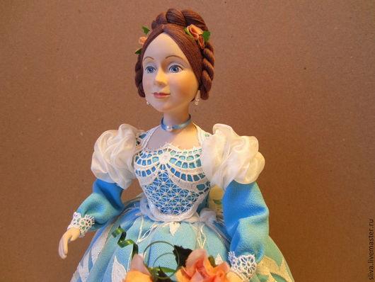 Приятная девушка в нежно-голубом платье, украшенном шитьём и вуалью. В волосах цветы. В руке небольшой букетик цветов. Кукла предназначена для сохранения тепла заварного чайника и аромата любимого ча