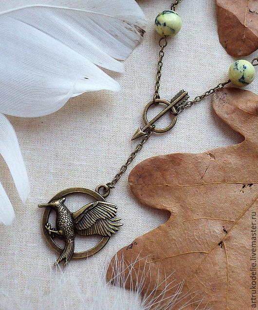 Кулон Сойка-пересмешница из фильма `Голодные игры` (Hunger Games) выполнен из фурнитуры цвета античной бронзы и бусин змеевика. Диаметр подвески с сойкой 2,5 см, длина цепи до кольца со стрелой 54 см