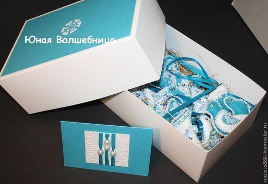 """Оригинальная упаковка. Белая коробка задекорирована дизайнерской бумагой голубого цвета и вырубленной снежинкой с примером наполнителя """"соломка""""."""