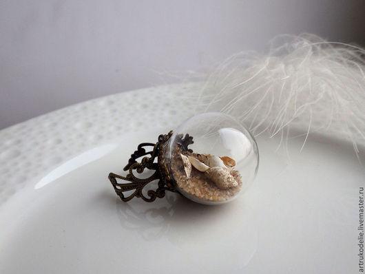 Кольцо Теплый берег. Полая стеклянная сфера заполнена настоящими песком и ракушками, воздухом, светом и запахом моря. Цвет фурнитуры - античная бронза. Кольцо безразмерное. Диаметр стеклянного шара - 2,5 см.