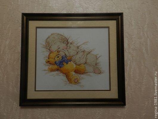 Картина вышита счетным крестом и офрмлена в рамку со стеклом.На картине изображен мальчик с мягкой игрушкой .Картина подходит как подарок новорожденному так и отличным интерьером в детской