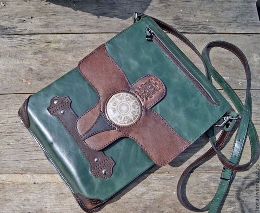 Сумочка из темно-зеленой кожи с коричневыми накладками из плотной кожи. На клапане есть небольшой карман  для очень нужных вещей.