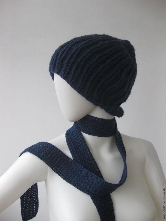 Модная объемная шапочка с нарочито грубоватыми `косичками` будет выглядеть интереснее, если сочетается с очень женственным узким и длинным шарфиком, повязанным классическим способом.