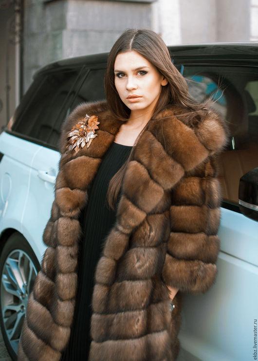 Соболье пальто медового цвета,прямого силуэта,диагональной раскладки шкурок.Пальто с  большим капюшоном.Рукава отстежные в 3/4-ти.На шубке брошь ручной работы,изготовлена руками под шубку.