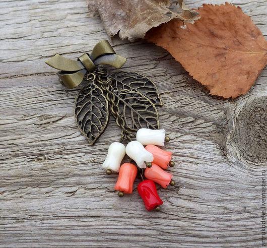 Изящная брошь выполнена из фурнитуры цвета античной бронзы и коралловых бусин трех оттенков в виде цветочных бутонов.