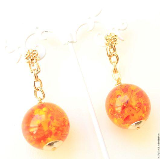 Стильное украшение – крупные серьги из янтаря медового цвета с позолоченной фурнитурой.