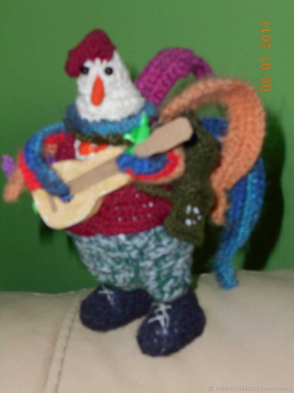 Петух Бенджамин. Первый парень на деревне. И спеть, и сыграть, и подраться. На нем крабовый берет, военные ботинки, малиновая жилетка и оранжевая бабочка.  В руках гитара, за спиной гармошка.
