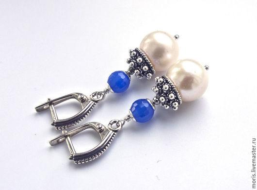 Очень заметные серьги, из крупного натурального пресноводного белого жемчуга, ярких  бусин  из голубого халцедона и красивых объемных шапочек из серебра мастеров Бали.