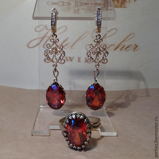Комплект украшений ручной работы с крупным ярко-красным гранатом и бесцветными фианитами состоит из серег и кольца.