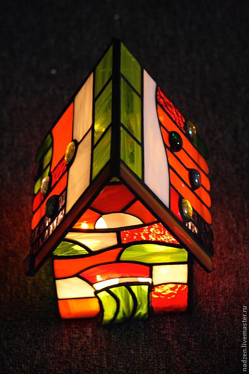 Домик из цветного стекла в витражной технике тиффани. Подсвечник рассчитан на 4 чайные свечи. Дверка открывается и ставятся свечки. Выполнен из стекла различной прозрачности и фактуры, преобладает красное и оранжевое. Материал: качественное американское стекло, никакого китайского.