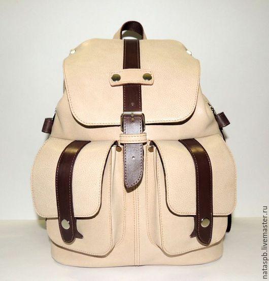 Удобный, прочный рюкзак сшит из мягкой плотной кожи крупного рогатого скота светло-бежевого цвета с коричневой отделкой.