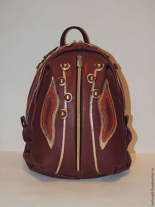 Рюкзачок выполнен из гладкой плотной итальянской кожи. Изделие оформлено аппликацией с присутствием кожи золотого цвета.