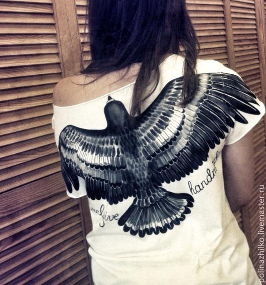 Покрой футболки позволяет носить её, обнажив одно плечо.