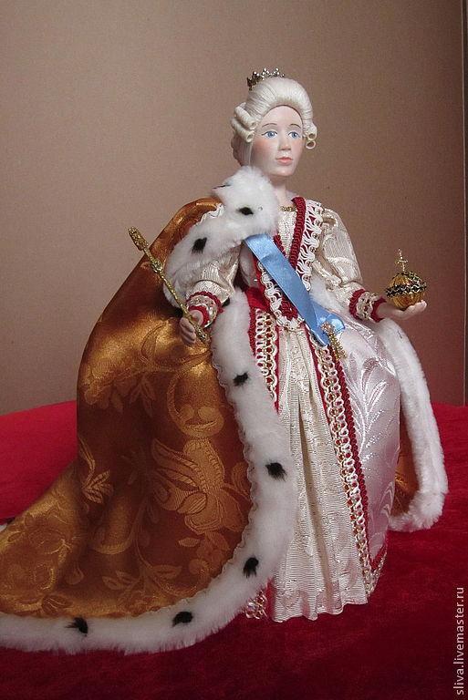 Кукла Императрица в парадном платье и мантии, подшитой горностаем. Корона и голубая лента через плечо.  В руках императрицы символы высшей власти - скипетр и держава.