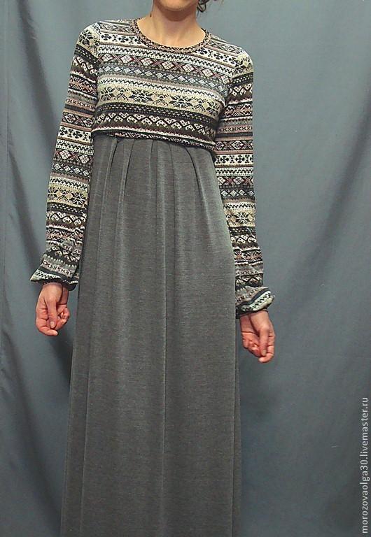 Длинное платье в пол из двух трикотажей-компаньонов производства Италии. Лиф выполнен из жаккардового итальянского трикотажа с узором в норвежском стиле (состав 82% акрил 18% шерсть), юбка - из мягкого и струящегося однотонного серого трикотажа ( 45% вискоза, 55% акрил) Платье может быть отрезным по линии талии, выигрышно подчеркивая ее, а можно сделать талию завышенной. Благодаря такому покрою платье отлично подойдет для беременных. Рукав длинный, собран на манжет.