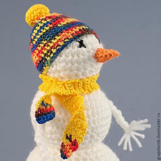 Неулыбчивый в простой шапочке с помпоном и шарфике в комплект.