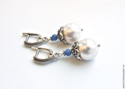 Очень заметные серьги из крупного натурального пресноводного белого жемчуга (13 мм ), ярких маленьких голубых бусин содалита и красивых объемных шапочек из серебра. Серебро ручной работы мастеров Бали